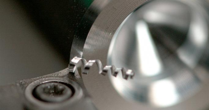 MACRO Shiny twisted shavings are made while a CNC machine threads a workpiece