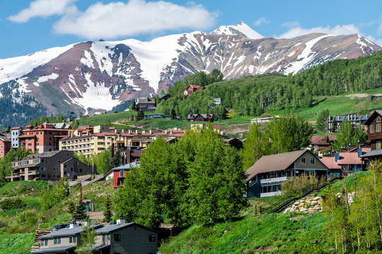 Mount Crested Butte snow marooon color mountain in summer with green lush color on hills slopes and houses cityscape