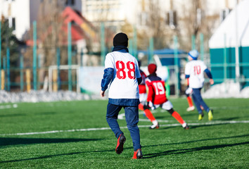 Boys in white and red sportswear plays  football on field, dribbles ball. Young soccer players with ball on green grass. Training, football, active lifestyle for kids , winter sport