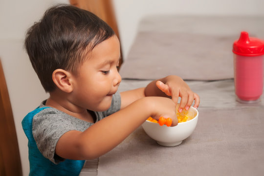 A cute toddler shows interest in eating a mac and cheese lunch, and holds spoon to self-feed.