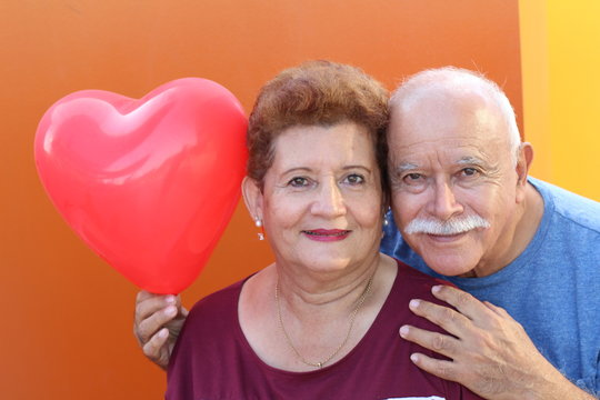 Senior Latino Couple holding a heart balloon