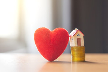 house model on coins stack with heart,saving and investment or family planning concept
