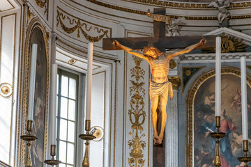 Realistic sculpture of Jesus on the cross decorating interior of catholic church in Italy