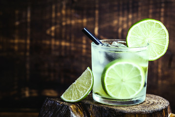 Fresh summer alcoholic caipirinha on a rustic wooden table, party drinks cocktail background. Space for text. Brazilian summer cold drink.
