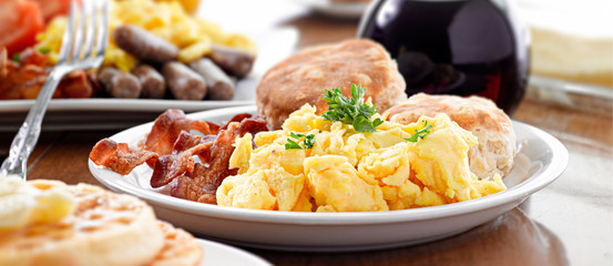 huge breakfast plate with scrambled eggs, bacon and biscuits