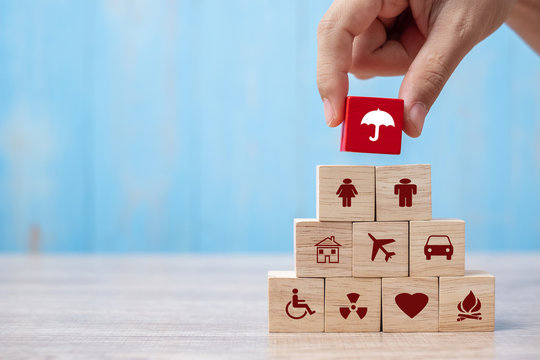 Hand holding umbrella wood block cover Insurance icon. healthcare medical, life, car, home, travel insurance concept