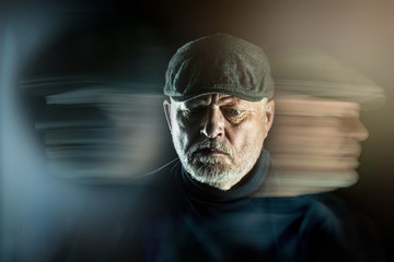 Portrait of a senior man with flat cap in front of black background. Ghostly faces surround him. Concept: surreal portrait