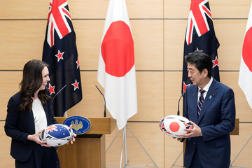 New Zealand's Prime Minister Jacinda Ardern and Japan's Prime Minister Shinzo Abe  exchange rugby balls after a joint press conference on September 19, 2019 in Tokyo