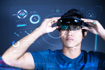 The Asian young man with virtual reality glasses experiences VR hololens headset in studio with advanced technology. Mixed reality concept of the future.