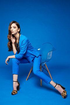 High fashion portrait of young elegant woman. Blue blouse, blue pants, curly hair, leopard shoes. .