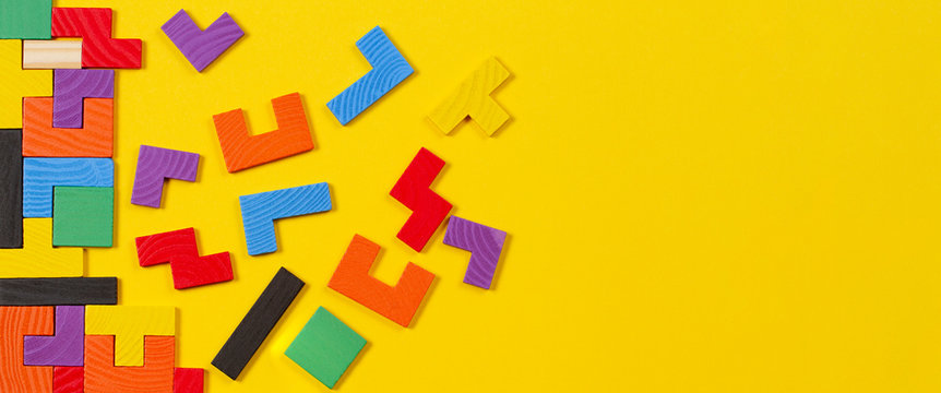 Different colorful shapes wooden blocks on yellow banner background. Top view