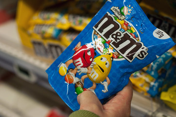 Mulhouse - France - 22 February 2018 - closeup of chocolate-coated peanuts from M & m's brand in hand at Super U supermarket