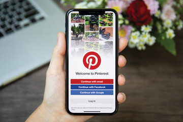 Woman hand holding iPhone X with social Internet service Pinterest