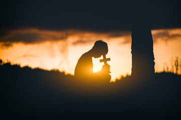 Young man praying and holding Cross under the tree at sunset background. christian silhouette concept.