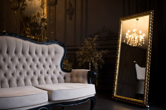 Ancient beige sofa in a dark room with a vintage mirror.