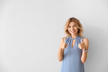 Portrait of beautiful woman showing thumb-up on light background