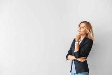 Portrait of beautiful thoughtful businesswoman on light background