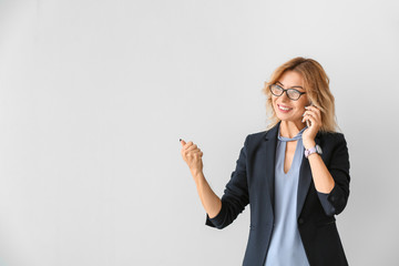 Portrait of beautiful businesswoman talking by phone on light background