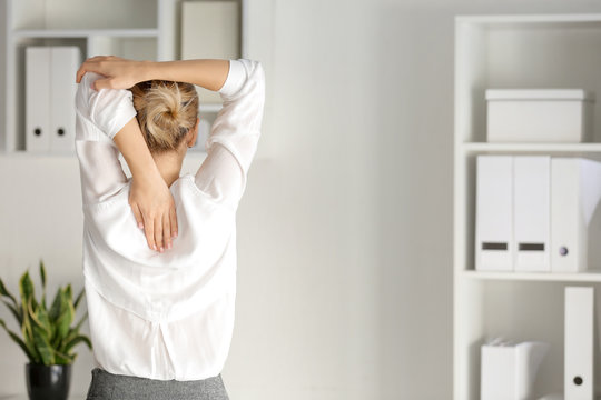 Young businesswoman practicing yoga in office, back view