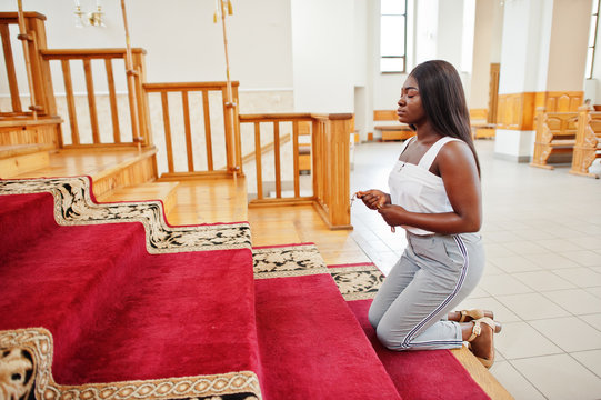 African american woman praying in the church. Believers meditates in the cathedral and spiritual time of prayer. Afro girl hold rosary and kneeling.