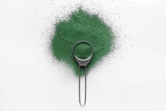 Scoop with spirulina powder on light background