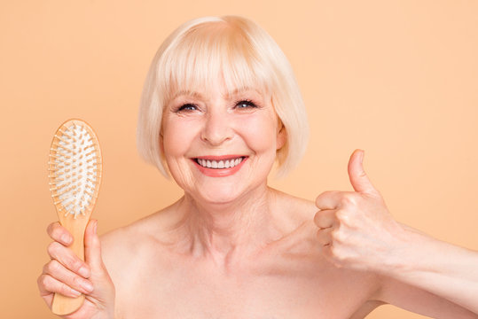 Close-up portrait of her she nice nude naked well-groomed confident cheerful cheery positive confident gray-haired lady showing new massage comb thumbup isolated over beige background