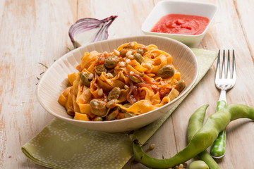 fettuccine pasta with broad bean tomato and pine nuts