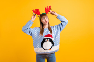 Look what I can do. Photo of very funny making faces squinting eyes see her nose teen hipster in retro big jumper jeans playing with toy decoration on red horns isolated bright color background