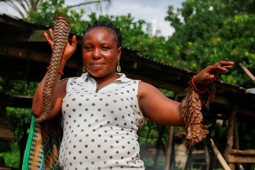 A bushmeat seller poses with scales of pangolin at a bushmeat market in Emure-ile, along Owo-Akure road Ondo