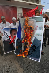 Palestinians burn pictures depicting Israeli PM  Netanyahu and Avigdor Lieberman during a protest demanding the release of Palestinian prisoners from Israeli jails, in the southern Gaza Strip