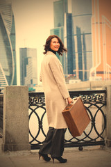 smiling woman in a bright coat with wooden case in her hand