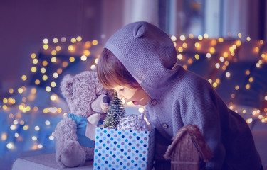 Christmas mood. Cute little excited child with teddy looking inside gift box with christmas toys and light from it with garland lights bokeh at background at home.  Purple violet magic toning.