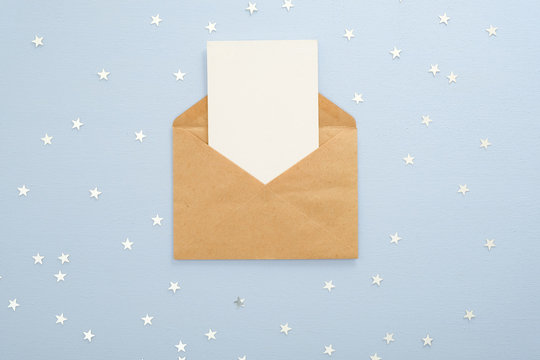 Empty blank card in kraft paper envelope on pastel blue background decorated with confetti star. Christmas, New Year, winter holiday invitation mockup.