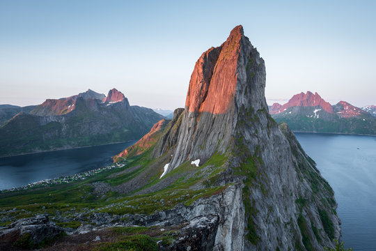 View from Mount Hesten on Iconic Mountain Segla in light of midnightsun in front of clear sky and mountain range in background, Fjordgard, Senja, Norway