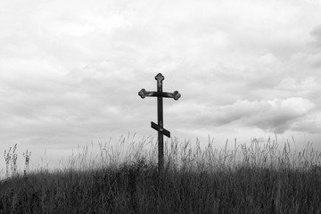 Black and white photo depicting Christian cross on hill against cloudy sky