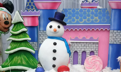 This image shows the decoration done at a stall of a kids festival with snowman standing beside a christmas tree while the mickey mouse is peeping in.