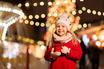 holidays, childhood and people concept - happy little girl with cup of tea at christmas market in winter evening