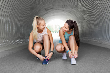 fitness, sport and healthy lifestyle concept - young women or female friends tying shoe laces outdoors
