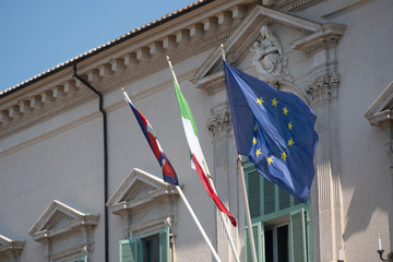 European and Italian flags and Italian Presidential pennant waving outside the Quirinale Palace in Rome, one of the three official residences of the President of the Italy