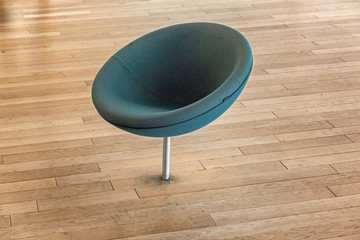 Round green chair mounted in the floor, public library Helsinki, Finland