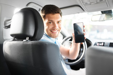 transport, driving and technology concept - man or car driver showing smartphone