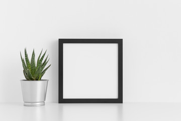 Black square frame mockup with a cactus in a pot on a white table.