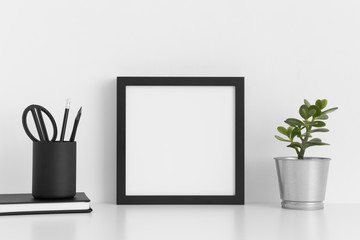 Black square frame mockup with a crassula in a pot and workspace accessories on a white table.