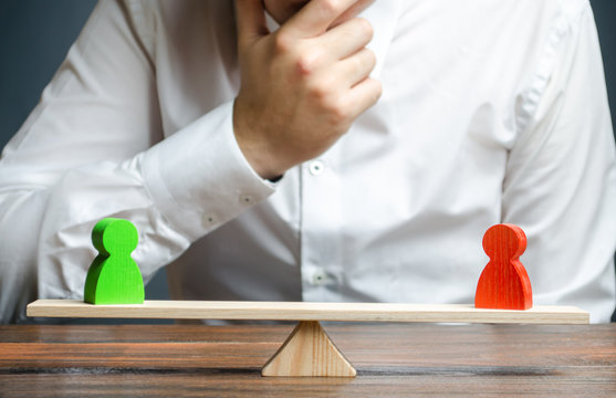 Man holds his hand on chin looks at the discussion process between red and green figures on a scales. Weighted decision. conflict resolution and the search for a compromise in the dispute.