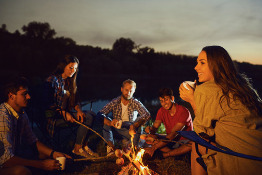 Girl with a mug of tea against the backdrop of friends by the bonfire at night