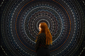 A gallery assistant poses in front of 'The Creator' by Damien Hirst at the White Cube in London