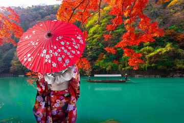 Keuken foto achterwand Rood Asian woman wear Kimono and watch The leaves change color. Boatman on the Katsura River on both sides is full of beautiful colorful trees
