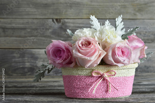 Mothers Day roses. Pink roses in basket on wooden background
