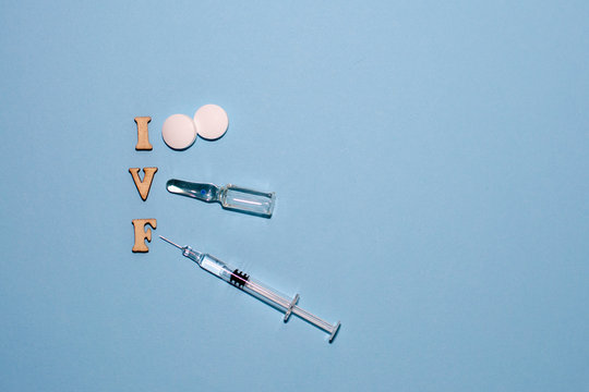 The abbreviation IVF is laid out in wooden letters on a blue background. In vitro injection pen, tablet and ampoule. A syringe with a thin huge. IVF concept. Medication with hormones. Infertility.