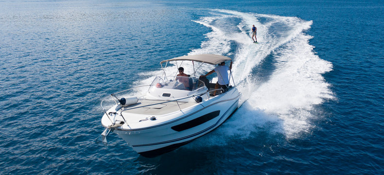 Speedboat with wakeboard rider on open sea